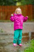 Happy little girl plays in a puddle — Stock Photo