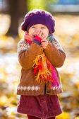 Happy little girl playing in the autumn park — Stock Photo
