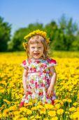 Little girl on the dandelion field — Stock Photo
