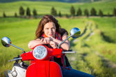 Young woman traveling by a scooter — Stock Photo