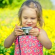 Little girl taking pictures on a meadow — Stock Photo #70104525