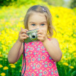 Little girl taking pictures on a meadow — Stock Photo #70104549