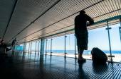 Silhouette of passengers waiting on open terrace in airport — Stock Photo