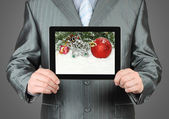 Man holds tablet PC with Christmas composition — Stock Photo