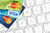 Cards Visa and MasterCard are placed on white keyboard background — Stock Photo
