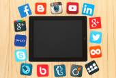 Famous social media icons placed around iPad on wooden background — Stock Photo