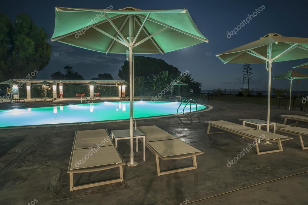 Piscina hamacas y sombrillas en la noche fotos de stock for Sombrillas para piscinas