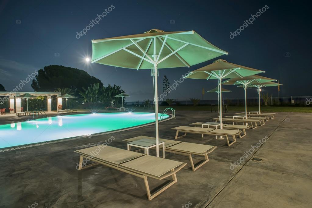 Piscina hamacas y sombrillas en la noche foto de stock for Hamacas de piscina