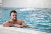 Man leaning at edge of swimming pool — Stock Photo