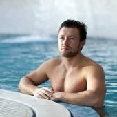 Man leaning at edge of swimming pool — Foto de Stock