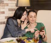 Two women using a smart phone — Stock Photo