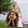 Young mother and daughter laying on the grass — Stock Photo #70404113