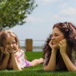 Young mother and daughter laying on the grass — Stock Photo #70404119
