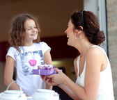 Little beautiful pretty girl giving a gift to her happy mother - indoors — Stock Photo