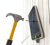 Hammer and digital tablet on wooden desk with nails concept background — Stock Photo