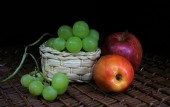 Still life of fruit: green grapes and red apples on a black background — Stock Photo