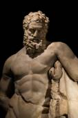 A statue of powerful Hercules, closeup, isolated in black — Stock Photo