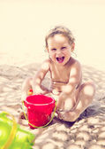 Laughing baby girl on a beach (toned) — Stock Photo