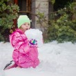 Cute blonde girl holding a huge snowball — Stock Photo #65594225