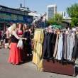 Women looking for second hand clothes and used items on the open air flea market — Stock Photo #53292769