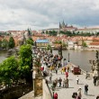 Tourists go on the Charles Bridge under the clouds — Stock Photo #53308837