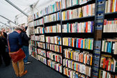 Happy students choose books at the indoor second hand market — Stock Photo