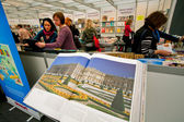 Many women look at new art books at the indoor book fair — Stock Photo
