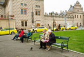 Couple of elderly tourists sit on the bench and read a guidebook about old city — Stock Photo