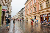 People with umbrellas walking under the rain in old houses — Stock Photo