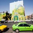 Traffic on sunny road with colorful taxi cars and street art on the building wall — Stock Photo #67151769