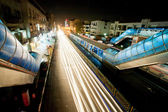 Motion blur light lines of rushing cars on the bright street of night city. — Stock Photo