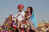Boy and girl driving the camel on the traditional Desert Festival — Stock Photo