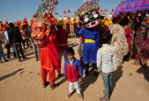 Children in carnival crowd with evil characters of Hinduism — Stock Photo