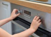Dangerous situation in the kitchen. Child playing with electric oven. — Stock Photo