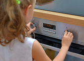 Dangerous situation in the kitchen. Child playing with electric oven. — Stockfoto