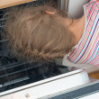 Little girl putting head into dishwasher. Dangerous situation at home. — Stock Photo #51840083