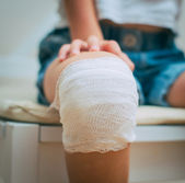 Child knee with adhesive and gauze bandage. — Stock Photo