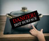 Child touches hot pan on the stove. Dangerous situation at home.  — Stock Photo