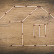 House made from matches on wooden tabletop. — Stock Photo #52388941