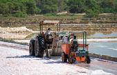 Sea salt production. Salt evaporation pond with tractor. — Stock Photo