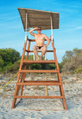 Man sitting on lifeguard tower on the beach. — Photo