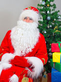 Santa Claus with gifts near the Christmas tree. — Stock Photo