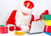 Santa Claus checking wishlist at his workshop. — Foto de Stock