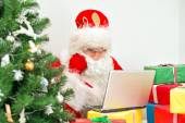 Santa Claus is using laptop at his workshop. — Stock Photo