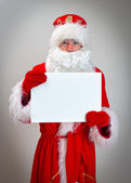 Pathetic Santa Claus is holding white blank. — Stock Photo