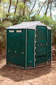 Green plastic toilet booth in the forest. — Stok fotoğraf