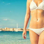 Part of suntanned woman body against bay. — Stock Photo