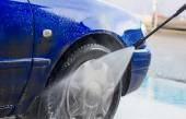 Blue car wash using high pressure water jet. — Stock Photo