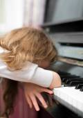 Child tired of learning the piano. — Stock Photo