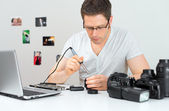 Male photographer soldering lens at his workplace. — Stock Photo